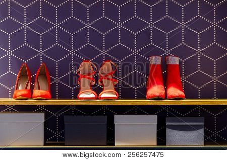 Red Shoes On Shelf In Store With Dark Background And Some Boxes
