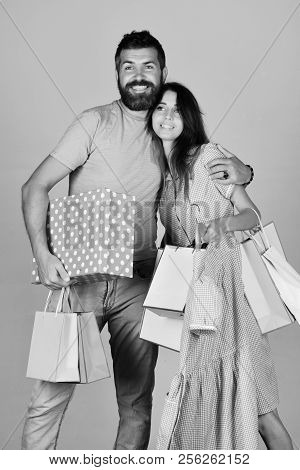 Guy With Beard And Girl With Smiling Faces Do Shopping. Couple In Love Holds Shopping Bags On Light