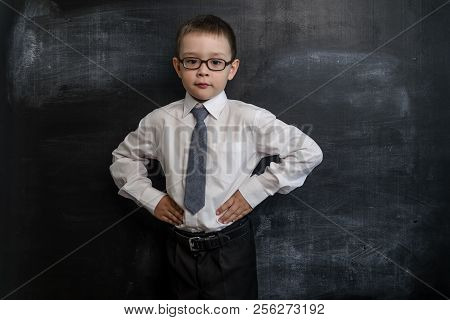 Young Kid's Standing Near A Blackboard With His Hands In The Sides, Bossy Pose. Back To School Conce