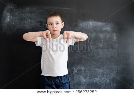 Young Kid's Standing Near A Blackboard Showing No Sign. Back To School Concept. Smart And Clever Pre