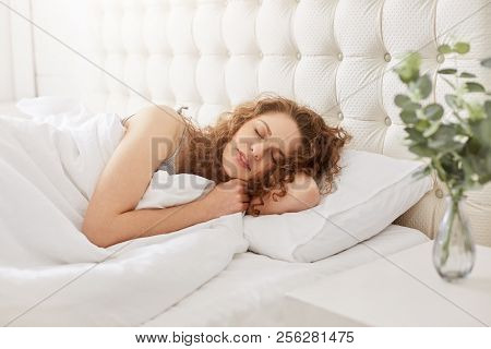 Shot Of Curly Lovely Girl Has Pleasant Dreams And Health Sleep In White Bed, Enjoys Good Rest In Hot