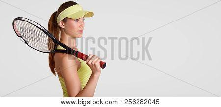 Sideways Shot Of Thoughtful Woman Has Healthy Clean Skin, Keeps Racquet On Shoulder, Wears Tennis Ca