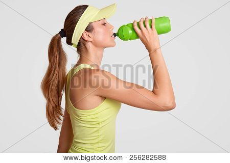 Sideways Shot Of Exhausted Tennis Player Drinks Water As Feels Thirrsty After Active Game, Has Fit B