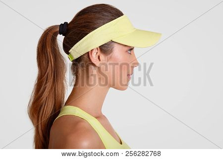 Indoor Shot Of Thoughtful Tennis Player Stands Sideways, Wears Sportsclothes, Has Pony Tail, Poses A