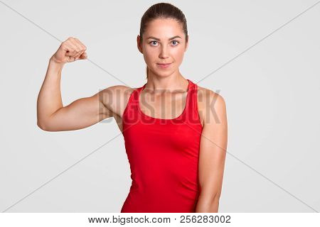 Horizontal Shot Of Self Determined Young Sportswoman In Red T Shirt, Shows Her Muscles, Has Training