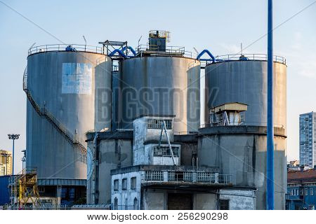 Silos Of Storage Of Silver Color And Old Factory Structure In Front Of Them