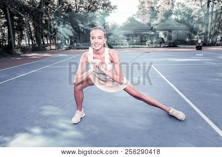 Jovial Enthusiastic Female Player Performing Warm Up