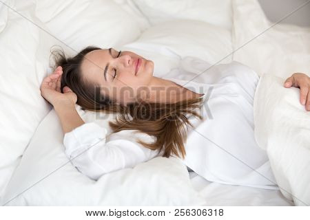 Beautiful Young Woman Sleeping Well In Cozy Comfortable Soft Bed