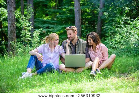 Company Youth Spend Leisure Outdoors With Laptop. Friends Working With Laptop At Green Meadow. Moder