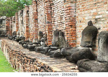 Kopflose und armlose Buddha Statuen sitzen in einem zerstörten Tempel in Ayutthaya, Thailand