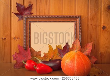 Fresh Vegetables, Autumn Maple Leaves And Picture Frame On Wooden Background