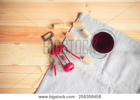 Glass Of Red Wine, Wine Corks  And Corkscrew On Wooden  Background. Top View, Copy Space.