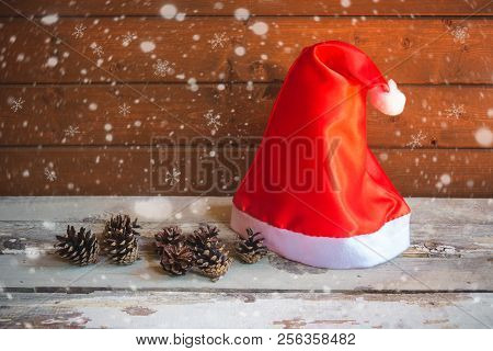 Santa Hat With Pine Cones On Aged Wooden Table