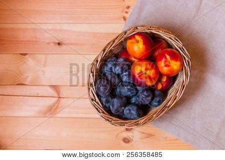 Wicker Basket With Nectarines And Plums On Wooden Background. Top View.