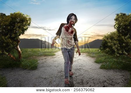 Angry Zombie Man With Bloody Mouth Walk Around At Outdoor. Halloween Concept