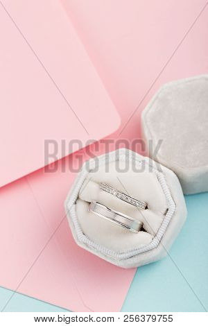 Two Silver Wedding Rings With Diamonds In White Velvet Jewelry Box. White Gold Rings With Gems On Pi
