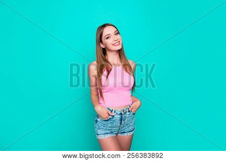 Studio Shot Of A Brunette Girl Who Stands And Looks Into The Camera Holding Her Hands In Her Pockets