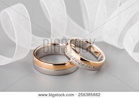Two-tone Wedding Rings With Ribbon. Rose Gold And Silver Rings On Gray Background