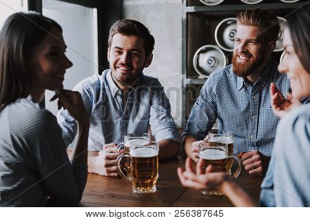 Company Friends Sitting And Drinking Beer In Pub. Happy Friends Drinking Beer And Clinking Glasses A