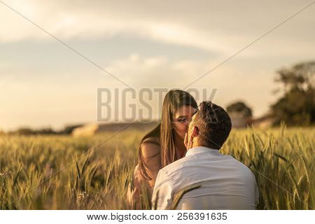 Will you marry me? Men making proposal for his girlfriend at gold wheat field