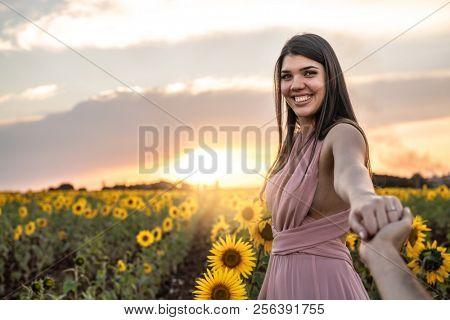 Boyfriend holding hands leading Girlfriend a field of flowers