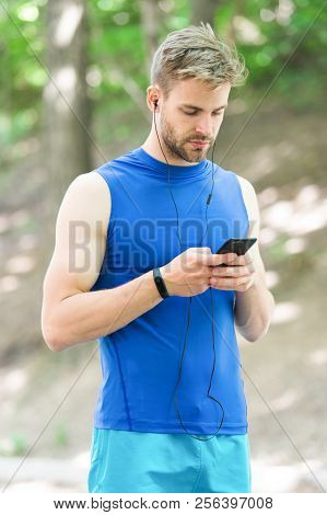Man Athlete On Busy Face Set Up Play List, Nature Background. Sportsman Training Pedometer And Headp