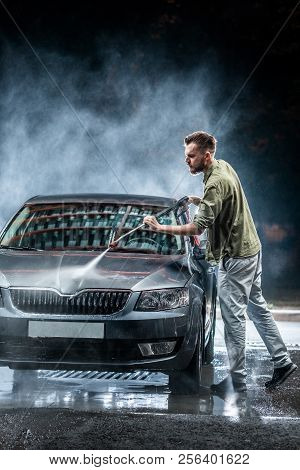 A Car Washer Washes A Gray Car With A High-pressure Washer At Night On The Street. Expensive Adverti