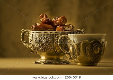 A vintage bowl of dates and a cup of tea.