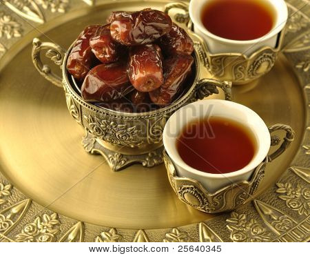 A golden bowl of dates and tea