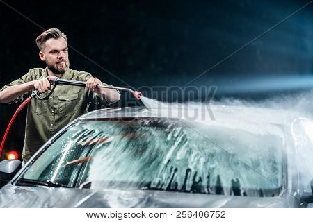 A Man With A Beard Washes A Gray Car With A High-pressure Apparatus At Night In A Car Wash. Expensiv