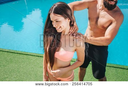 Beautiful Girl Is Smiling. She Stands In Swimsuit Bikini And Looks Down. Girl Smiles. Guy Stands Beh