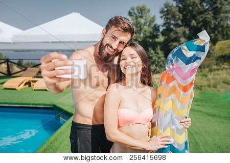Nice Picture Of Bearded Guy And Well-built Girl Standing And Posing On Camera. They Take Selfie On P