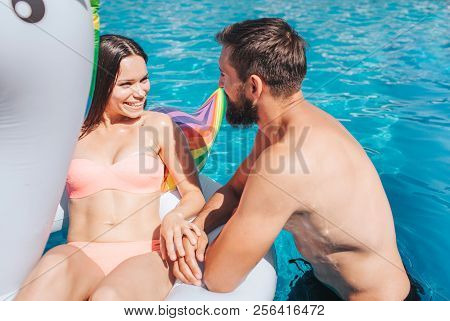 Positive Picture Of Gorgeous Couple Swimming In Pool. Girl Is Lying On Air Mattress. They Look At Ea