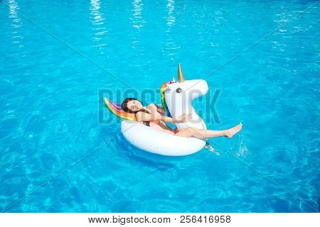 Happy And Positive Young Woman Is Lying On Air Mattress In The Middle Of Swimming Pool. She Waves Wi