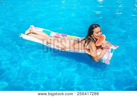 Happy Girl Is Lying On Air Mattress And Eat Piece Of Watermelon. She Smiles. Girl Is In Swimming Poo
