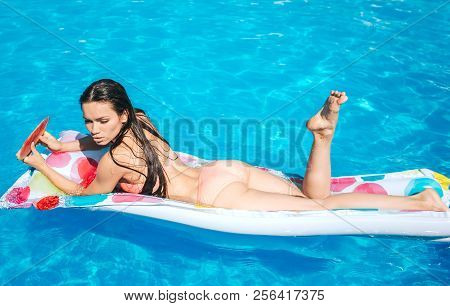 Slim And Well-built Girl Is Lying On Air Mattress And Look Down. She Is In Swimming Pool. Girl Hodls