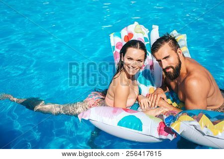 Nice And Young Couple Is Leaning On Air Mattress And Look On Camera. They Pose. Girl Is Smiling. Guy