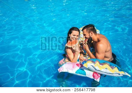 Nice Picture Of Couple Leaning To Air Mattress And Eating Watermelon. They Look At Each Other. Coupl