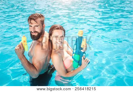 Godd-looking Man And Woman Stand In Swimming Pool And Look On Camera. They Pose And Smile. People Ho