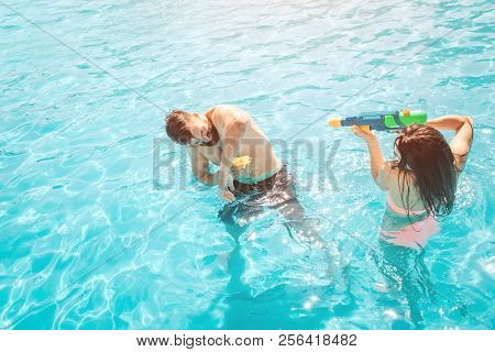 Funny Picture Of Couple Playing In Swimming Pool. Girl Is Shooting In Guy From Water Gun. He Tries T
