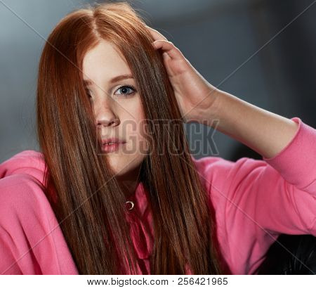 Closeup portrait of attractive young ginger-haired girl looking at camera hand in hair.
