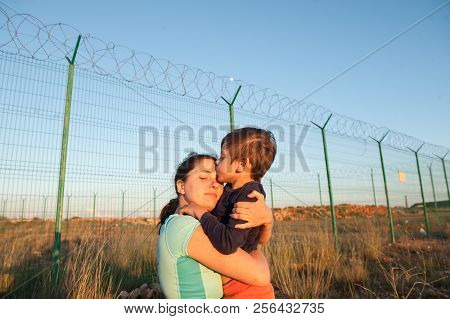 Happy Caucasian Mother Refugee Reunited With Child Kissing Her Near Fence Barbed Wire