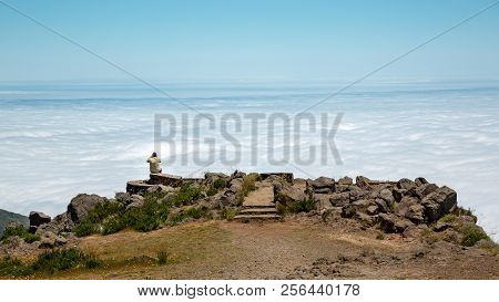 Man Sitting With His Back On Edge Of Cliff Above The Clouds And Takes Photo. Mountain Landscape. On