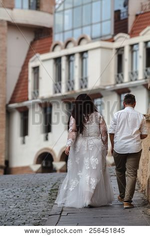 Groom And Plus Size Bride Walking Through Field Evening