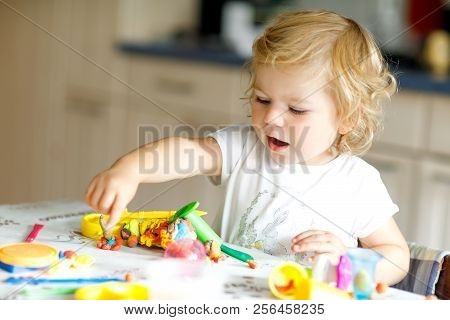 Adorable Cute Little Toddler Girl With Colorful Clay. Healthy Baby Playing And Creating Toys From Pl