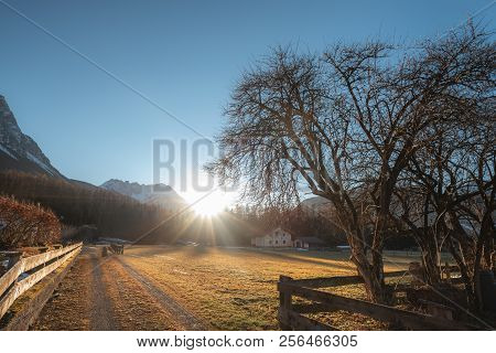 Landscape With The Sun And Its Rays Shining And Warming The Austrian Alps, The Leafless Trees, On A