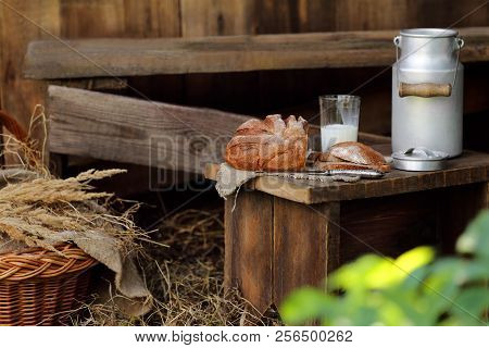 A Loaf Of Rye Bread And A Can Of Milk On A Bench In The Garden