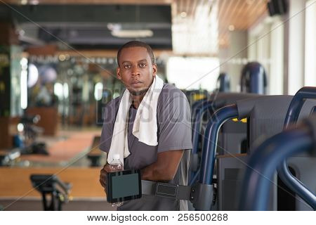 Serious Man Leaning On Gym Equipment, Holding Water Bottle And Looking Away. Serious Black Guy Weari