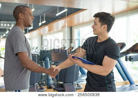 Smiling Black Man Thanking Personal Trainer In Gym. Young Guy Greeting Instructor With Gym Equipment