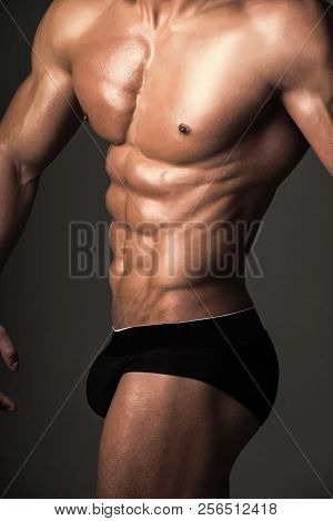 Sport And Workout. Man With Muscular Body And Torso. Athletic Bodybuilder Man On Grey Background. Co